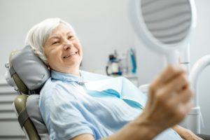an older woman smiling in the dentist's chair after receiving dental implants