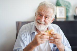 Man with dental implants eating burger