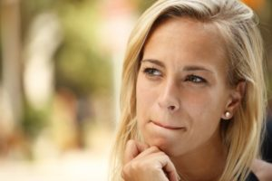 young woman thinking before giving in to bad dental habits